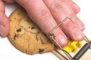 2503922-a-hand-caught-in-a-mousetrap-dieting-concept
