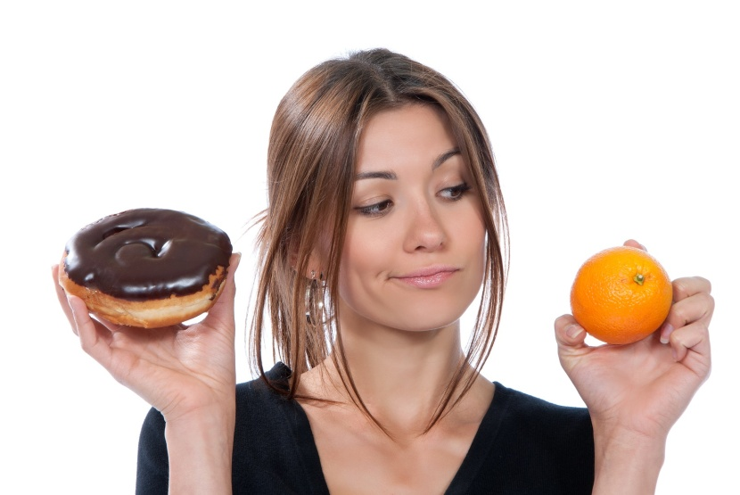 Healthy eating food concept. Woman comparing unhealthy donut and orange fruit thinking isolated on a white background