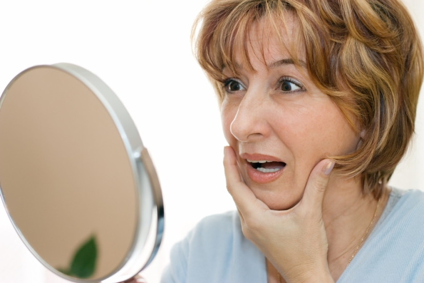 middle-age-woman-looking-worried-into-mirror