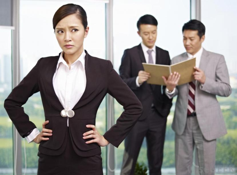 frowning-asian-woman-in-business-suit-with-two-asian-men-behind-her-looking-at-papers