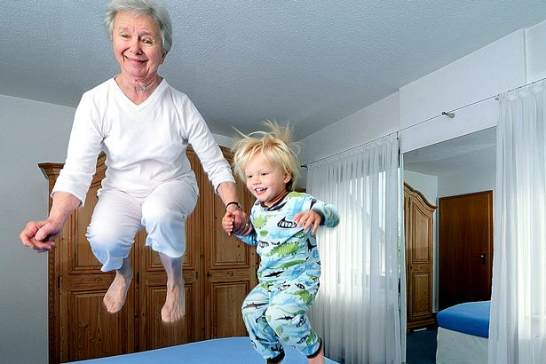 grandmother-and-boy-jumping-on-bed-in-pyjamas